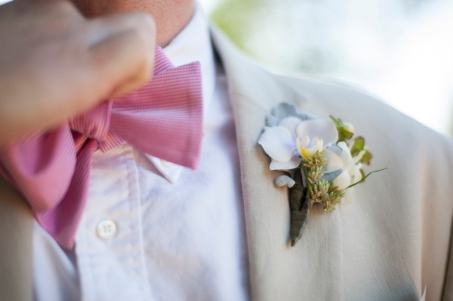 The groom's pink bow tie and white orchid boutineer.
